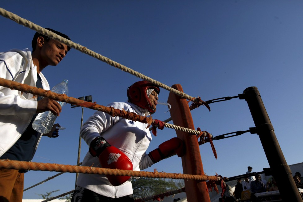 """Urooj, 15, spits water between rounds in her bout during the Sindh Junior Sports Association Boxing Tournament in Karachi, Pakistan February 21, 2016. For the past six months about a dozen girls, aged 8 to 17, have gone to the Pak Shine Boxing Club after school to practice their jabs, hooks and upper cuts. Pakistani women have been training as boxers in small numbers and competed in the South Asian Games last year, said Younis Qambrani, the coach who founded the club in 1992 in the Karachi neighbourhood of Lyari, better known for internecine gang warfare than for breaking glass ceilings. REUTERS/Akhtar Soomro SEARCH """"THE WIDER IMAGE"""" FOR ALL STORIES TPX IMAGES OF THE DAY"""