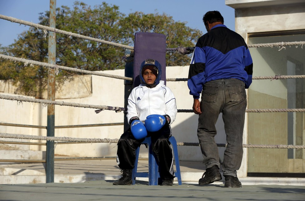 """REFILE - CLARIFYING NAME OF BOXING CLUBAamna, 11, waits for the start for her bout during the Sindh Junior Sports Association Boxing Tournament in Karachi, Pakistan February 21, 2016. For the past six months about a dozen girls, aged 8 to 17, have gone to the Pak Shaheen Boxing Club after school to practice their jabs, hooks and upper cuts. Pakistani women have been training as boxers in small numbers and competed in the South Asian Games last year, said Younis Qambrani, the coach who founded the club in 1992 in the Karachi neighbourhood of Lyari, better known for internecine gang warfare than for breaking glass ceilings. REUTERS/Akhtar Soomro SEARCH """"THE WIDER IMAGE"""" FOR ALL STORIES"""