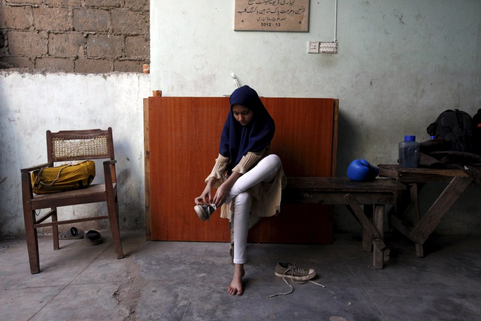 """REFILE - CLARIFYING NAME OF BOXING CLUBTabia, 12, removes her shoes after finishing an exercise session at the first women's boxing coaching camp in Karachi, Pakistan February 19, 2016. For the past six months about a dozen girls, aged 8 to 17, have gone to the Pak Shaheen Boxing Club after school to practice their jabs, hooks and upper cuts. Pakistani women have been training as boxers in small numbers and competed in the South Asian Games last year, said Younis Qambrani, the coach who founded the club in 1992 in the Karachi neighbourhood of Lyari, better known for internecine gang warfare than for breaking glass ceilings. REUTERS/Akhtar Soomro SEARCH """"THE WIDER IMAGE"""" FOR ALL STORIES"""