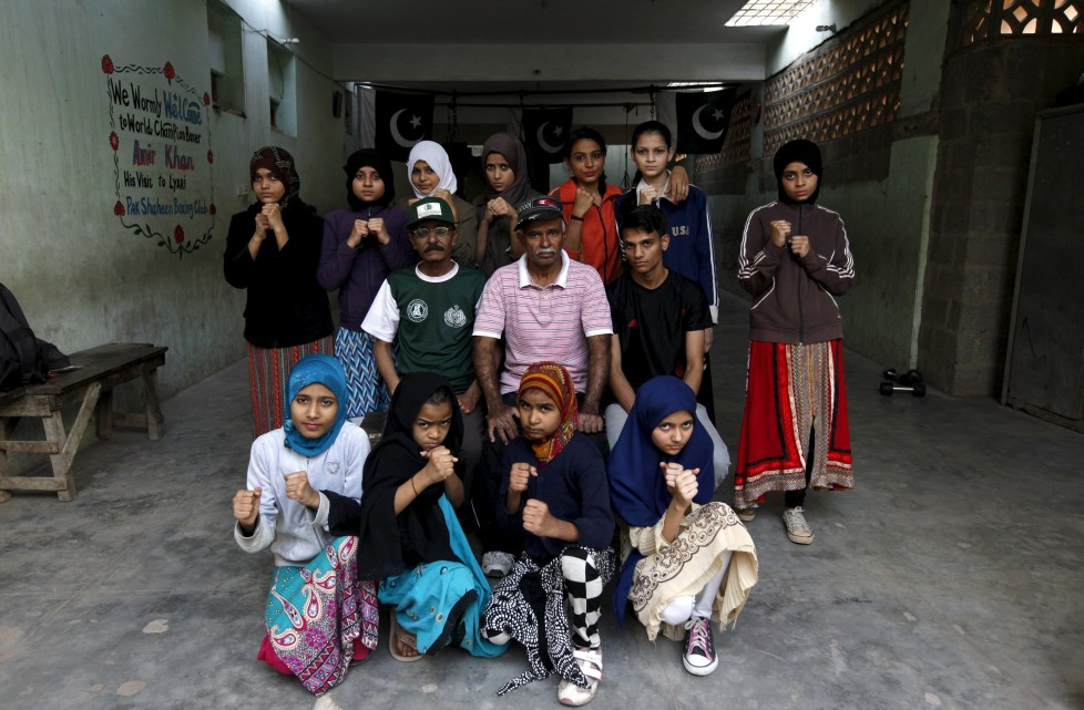 """REFILE - CLARIFYING NAME OF BOXING CLUBGirl trainees pose for a group photograph with their coach Yunus Qambrani and assistant coach Nadir at the first women's boxing coaching camp in Karachi, Pakistan February 20, 2016. For the past six months about a dozen girls, aged 8 to 17, have gone to the Pak Shaheen Boxing Club after school to practice their jabs, hooks and upper cuts. Pakistani women have been training as boxers in small numbers and competed in the South Asian Games last year, said Younis Qambrani, the coach who founded the club in 1992 in the Karachi neighbourhood of Lyari, better known for internecine gang warfare than for breaking glass ceilings. REUTERS/Akhtar Soomro SEARCH """"THE WIDER IMAGE"""" FOR ALL STORIES"""