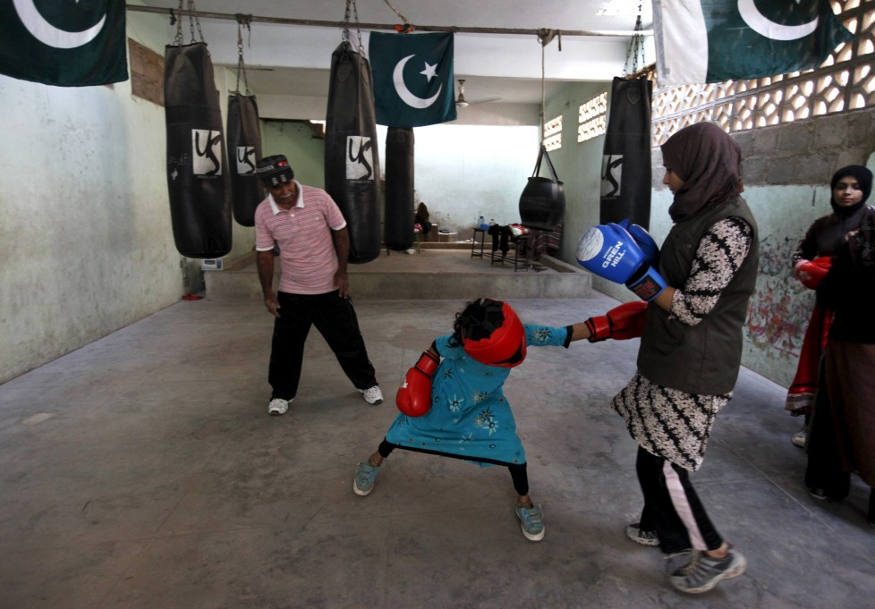 """REFILE - CLARIFYING NAME OF BOXING CLUBArisha, 9, punches Misbah during an exercise session at the first women's boxing coaching camp in Karachi, Pakistan February 20, 2016. For the past six months about a dozen girls, aged 8 to 17, have gone to the Pak Shaheen Boxing Club after school to practice their jabs, hooks and upper cuts. Pakistani women have been training as boxers in small numbers and competed in the South Asian Games last year, said Younis Qambrani, the coach who founded the club in 1992 in the Karachi neighbourhood of Lyari, better known for internecine gang warfare than for breaking glass ceilings. REUTERS/Akhtar Soomro SEARCH """"THE WIDER IMAGE"""" FOR ALL STORIES"""
