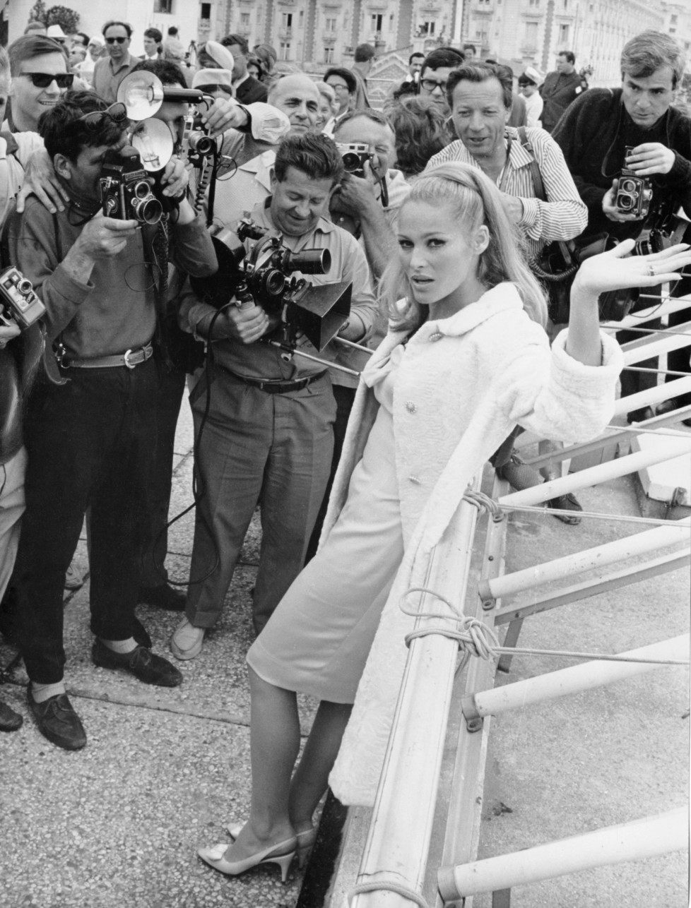ZUM 80. GEBURTSTAG DER SCHWEIZER FILMSCHAUSPIELERIN URSULA ANDRESS AM SAMSTAG, 19. MAERZ 2016, STELLEN WIR IHNEN FOLGENDES BILDMATERIAL ZUR VERFUEGUNG - Press photographers surround Swiss-born actress Ursula Andress on the Croisette seafront, Cannes, on May 21, 1965, after her arrival to attend the International Film Festival. (AP Photo/Levy)