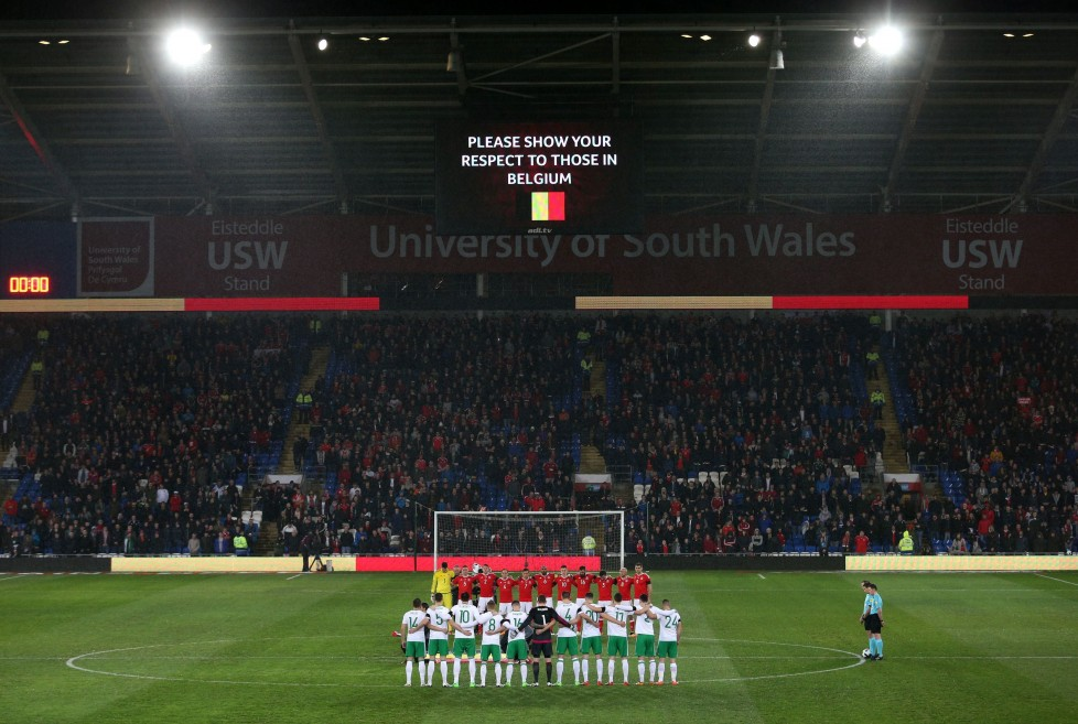 Wales' and the Northern Ireland, front, soccer teams, pose for a minutes silence in memory of the victims of the Belgium terror attacks as the stadium is lit in the colours of the Belgian flag prior to the International Friendly at the Cardiff City Stadium, Cardiff, Wales, Thursday March 24, 2016. (David Davies/PA via AP) UNITED KINGDOM OUT NO SALES NO ARCHIVE