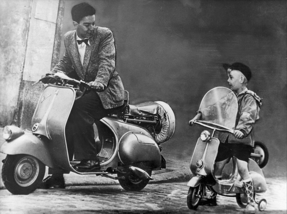 GERMANY - SEPTEMBER 02: A kid on a toy vespa scooter beside to a young man on vespa scooter motorcycle in 1953. (Photo by Keystone-France/Gamma-Keystone via Getty Images)