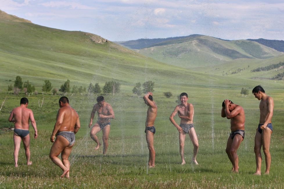 Mongolian wrestlers take an outdoor shower at the end of a train session at a camp in the grassland town of Suuj, about 60 km north of the capital Ulan Bator, July 5, 2006. Mongolians celebrate their annual festival of Naadam, a paegant of wrestling, hoseback-riding and archery, on July 11. This year's will be bigger than ever as Mongolians mark 800 years since Genghis Khan united the nation. REUTERS/Nir Elias (MONGOLIA) BEST QUALITY AVAILABLE Also see image: GM1DSZERTCAA - RTR1FIL4
