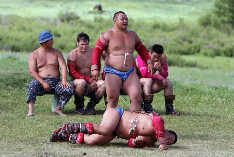 Mongolian wrestlers train at a camp in the grasslands town of Suuj, about 60 km (37 miles) north of the capital Ulan Bator, July 5, 2006. Mongolians celebrate their annual festival of Naadam, a pageant of wrestling, hoseback-riding and archery, on July 11. This year's will be bigger than ever as Mongolians mark the 800 years since Genghis Khan united the nation. REUTERS/Nir Elias (MONGOLIA) - RTR1F7QI