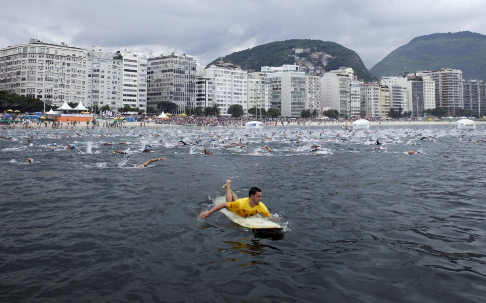 ZUM COUNTDOWN VON 100 TAGEN BIS ZUR EROEFFNUNGSZEREMONIE DER OLYMPISCHEN SOMMERSPIELE RIO 2016 AM MITTWOCH, 27. APRIL 2016, STELLEN WIR IHNEN FOLGENDES BILDMATERIAL ZUR VERFUEGUNG - A lifeguard paddles along participants of the annual Travessia dos Fortes or Fort Crossing swimming competition in Copacabana Beach in Rio de Janeiro, Brazil, Sunday April 3, 2011. About 2,000 swimmers took part in the 2.08 mile aquatic marathon between Fort Copacabana and Fort Rudder. (KEYSTONE/AP Photo/Victor R. Caivano)