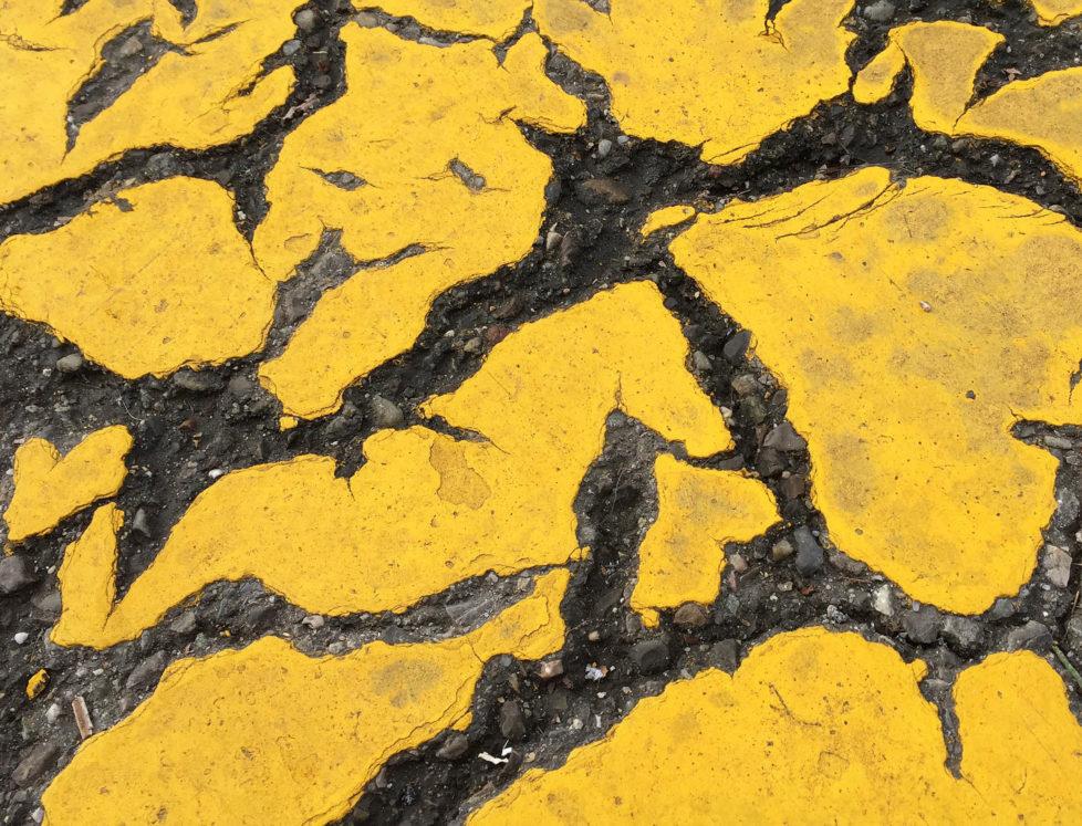 BeschŠdigte gelbe Farbschicht auf Asphalt; anregende Muster der Farbreste.
