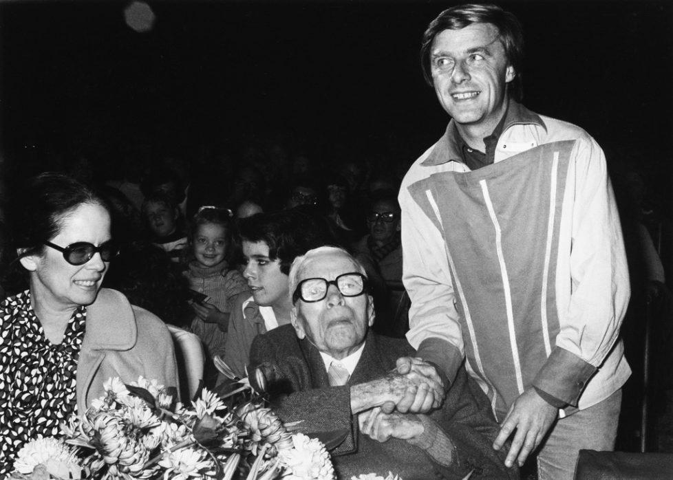 Der Schweizer Kabarettist und Gaststar des Circus Knie Emil Steinberger, rechts, schuettelt dem Schauspieler und Regisseur Charlie Chaplin, Mitte, die Hand, waehrend einer Auffuehrung des Circus Knie im Jahre 1977 in Vevey. Links im Bild ist Chaplins Ehefrau Oona Chaplin. (KEYSTONE/Str)