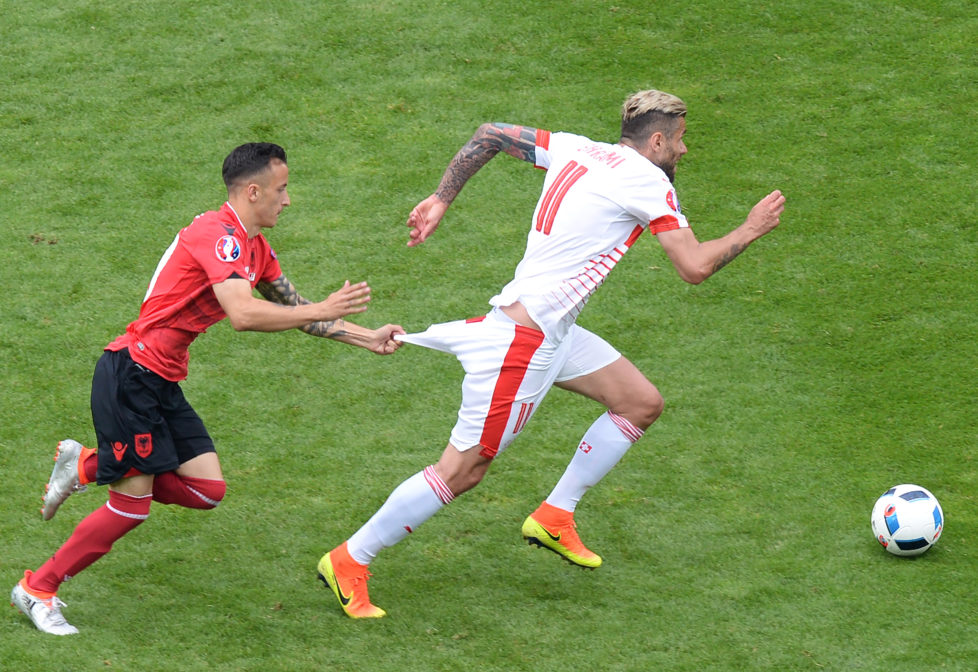 Albania's midfielder Ergys Kace (L) pulls down the shorts of Switzerland's midfielder Valon Behrami during the Euro 2016 group A football match between Albania and Switzerland at the Bollaert-Delelis Stadium in Lens on June 11, 2016. / AFP PHOTO / Denis CHARLET