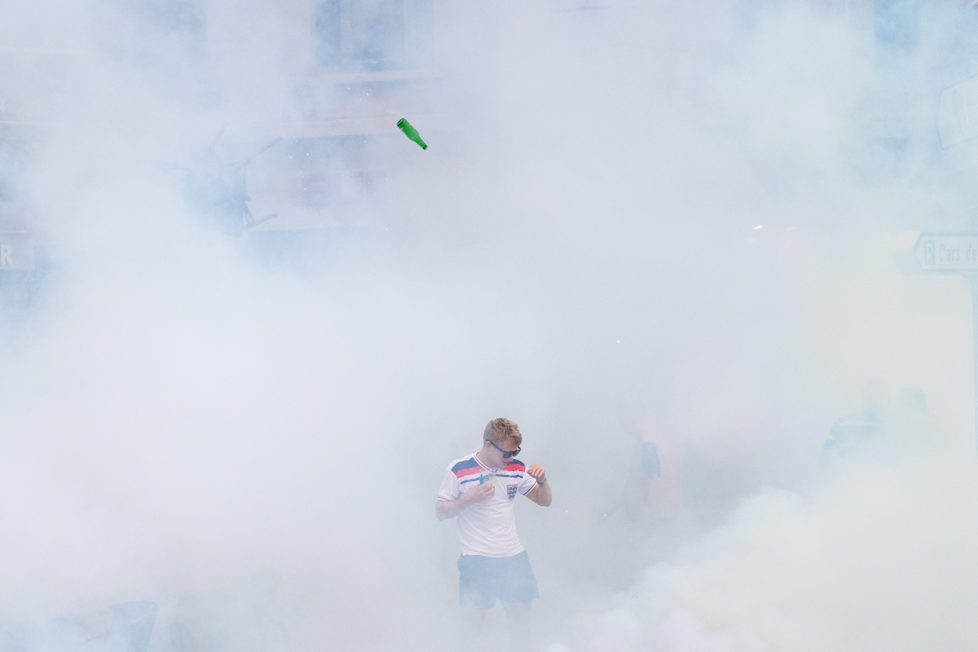 An England supporter walks as he is engulfed in tear gas during clashes with police in Marseille, southern France, on June 10, 2016, on the eve of England's Euro 2016 football match against Russia. / AFP PHOTO / LEON NEAL