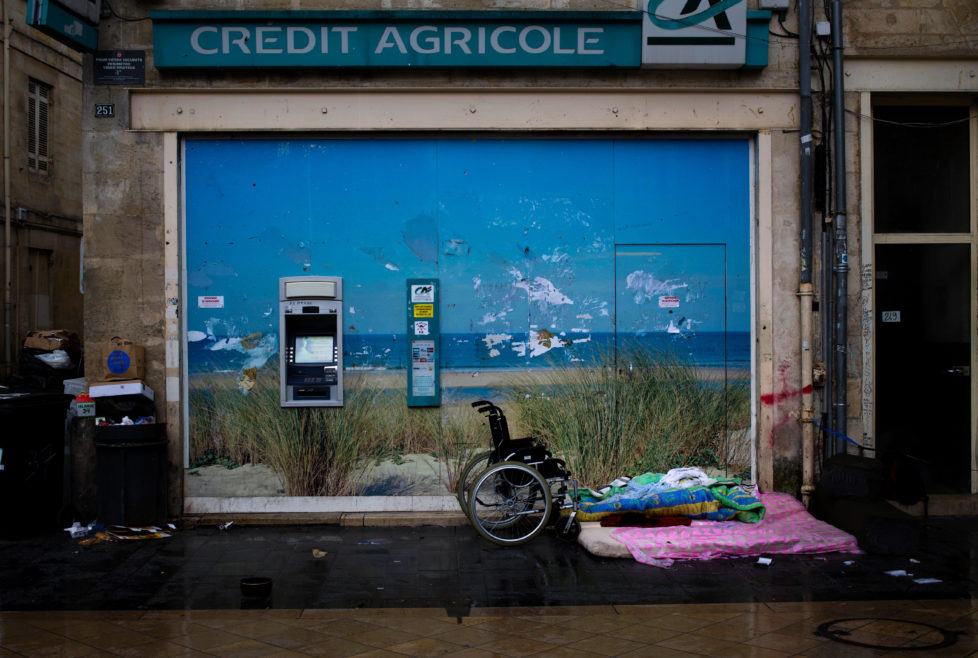 A mattress and wheelchair belongings of a homeless person are seen in front of an out of services ATM machine in down town of Bordeaux, France, Tuesday, June 14, 2016. (AP Photo/Hassan Ammar)