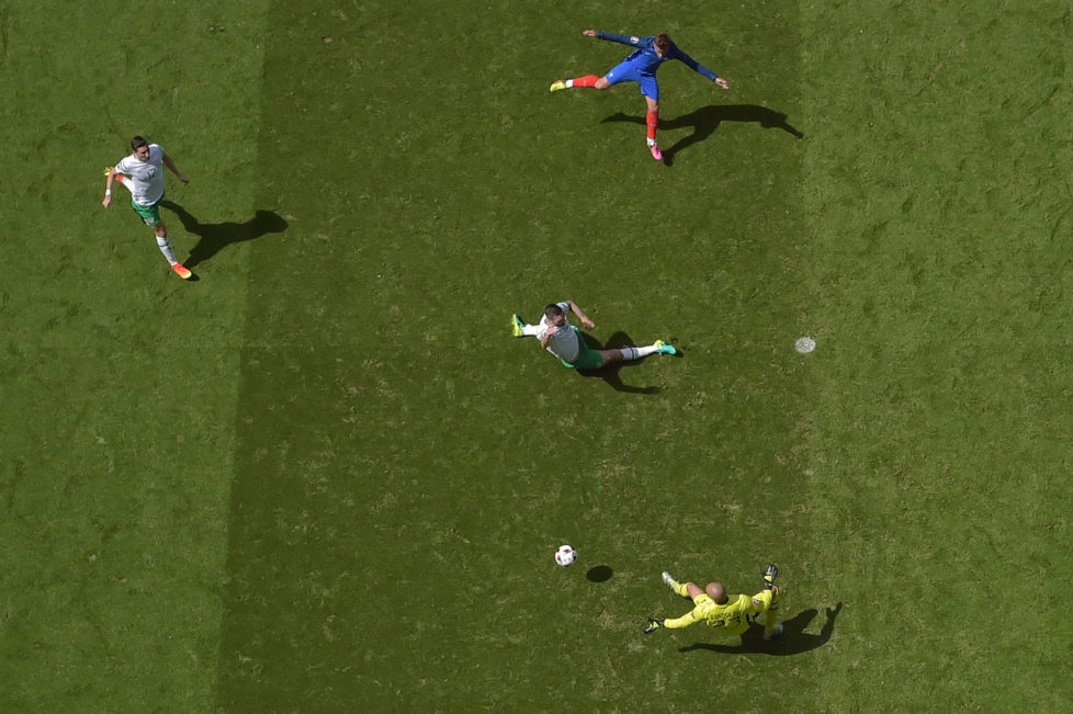 France's forward Antoine Griezmann (top) scores against Ireland's goalkeeper Darren Randolph (bottom) during the Euro 2016 round of 16 football match between France and Republic of Ireland at the Parc Olympique Lyonnais stadium in Décines-Charpieu, near Lyon, on June 26, 2016. / AFP PHOTO / Valery HACHE