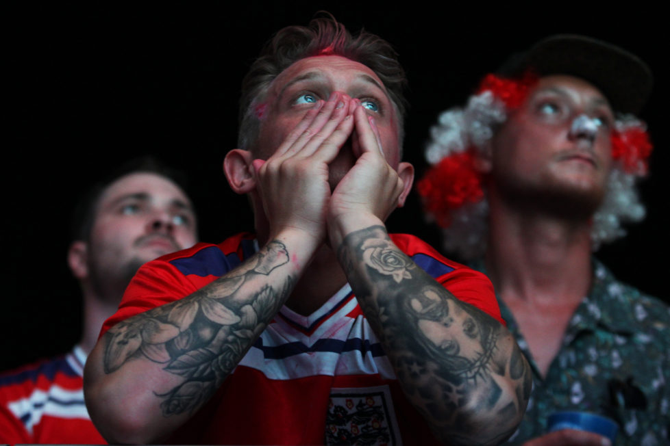 An England's fan is disappointed after the football match between Iceland and England at the Champ-de-Mars fan zone in Paris on June, 27, 2016. / AFP PHOTO / JEAN CHRISTOPHE MAGNENET
