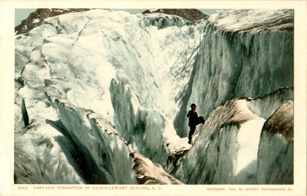 CANADA - CIRCA 1906: Postcard view of a man standing on giant crevasses in the glacier ice. (Photo by Lake County Museum/Getty Images)