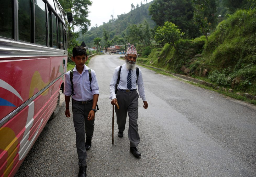 "Durga Kami, 68, who is studying tenth grade at Shree Kala Bhairab Higher Secondary School, walks with his classmate Sagar Thapa, 14, as they head to school in Syangja, Nepal, June 5, 2016. REUTERS/Navesh Chitrakar. SEARCH ""DURGA KAMI"" FOR THIS STORY. SEARCH ""THE WIDER IMAGE"" FOR ALL STORIES"