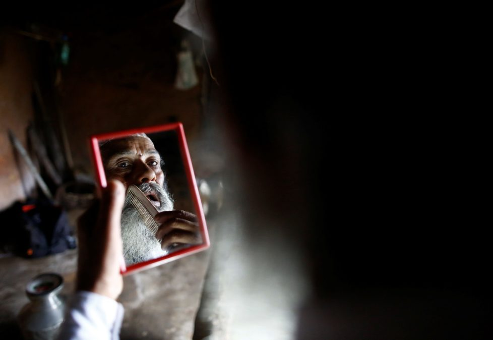 "Durga Kami, 68, who is currently studying tenth grade at Shree Kala Bhairab Higher Secondary School, looks into a mirror as he combs his beard while getting ready for school in Syangja, Nepal, June 5, 2016. Kami has promised his classmate Sagar Thapa that he will cut his beard off if he passes tenth grade. REUTERS/Navesh Chitrakar. SEARCH ""DURGA KAMI"" FOR THIS STORY. SEARCH ""THE WIDER IMAGE"" FOR ALL STORIES"