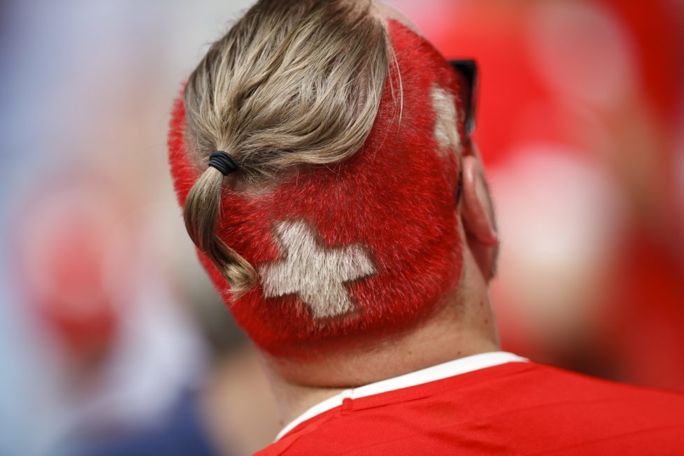 A Swiss fan, the colors of the national flag painted on his head, waits for the start of the Euro 2016 Group A soccer match between Romania and Switzerland at the Parc des Princes stadium in Paris, France, Wednesday, June 15, 2016. (AP Photo/Christophe Ena)