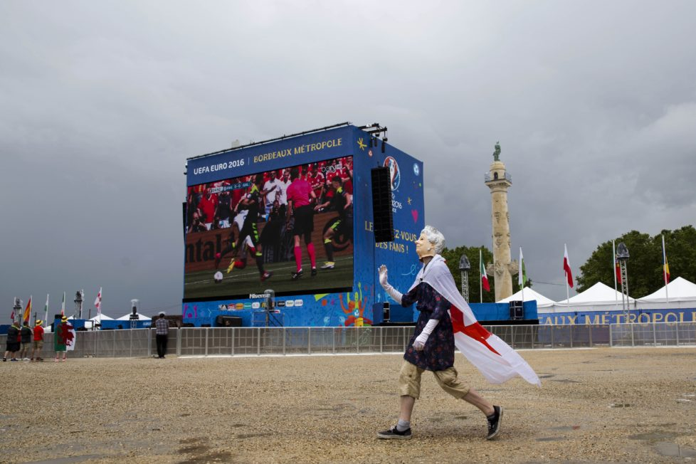 A British fan wearing a mask representing Britain's Queen Elizabeth II waves to other fans as they watch the Euro 2016 Group B soccer match between England and Wales in Bordeaux's fan zone, France, Thursday, June 16, 2016. (AP Photo/Hassan Ammar)