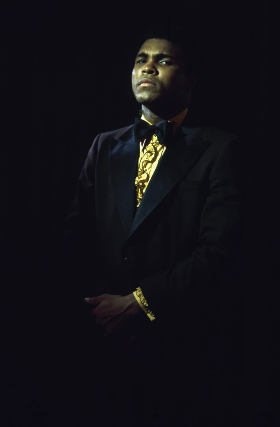 Portrait of American heavyweight boxer Muhammad Ali, in a tuxedo, ruffled yellow shirt, and bowtie, 1971. The portrait was taken prior to his first bout with Joe Frazier, where he unsuccessfully battled for the title belt on March 8, 1971 at Madison Square Garden. (Photo by John Shearer/The LIFE Picture Collection/Getty Images)