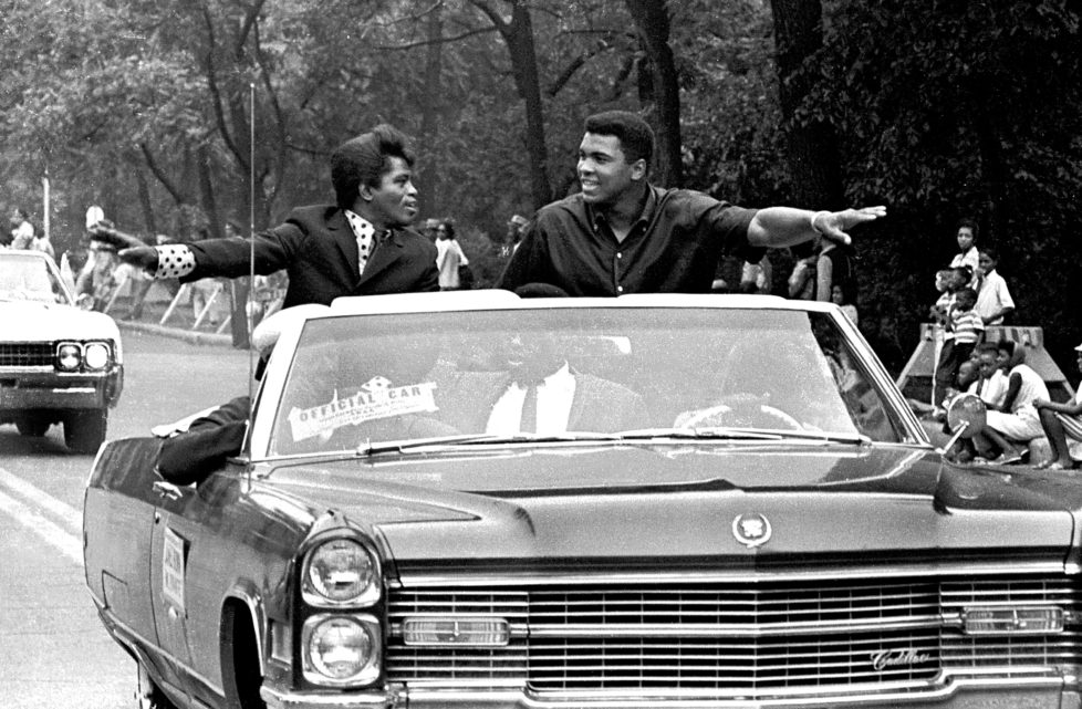 American singer James Brown (1933 - 2006) and boxing champ Muhammad Ali (then known as Cassius Clay), smile and greet parade goers while participating in the annual Bud Billiken parade, Chicago, Illinois, August 1966. (Photo by Robert Abbott Sengstacke/Getty Images)