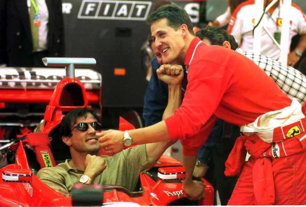 MTC04-19980522-MONACO - German Ferrari Formula 1 pilot Michael Schumacher (R) jokes with US film star Sylvester Stallone who sits in the cockpit of Schumacher's car during a training-free day of the Monaco Grand Prix here, 22 May. The race takes place 24 May. EPA PHOTO DPA/OLIVER MULTHAUP