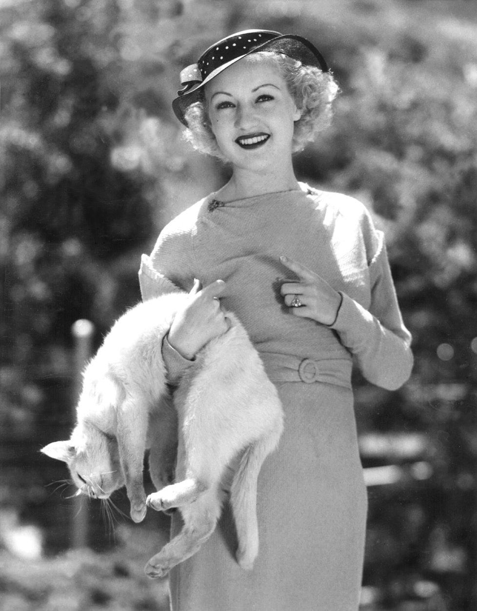 """Whitey shows Betty Grable how he can """"play dead"""", 1935. (KEYSTONE/Everett Collection/) IM BILD / BILDSEITE LIEBEN MICH MEINE KATZEN BUND 23.7. TAGI 26.7."""