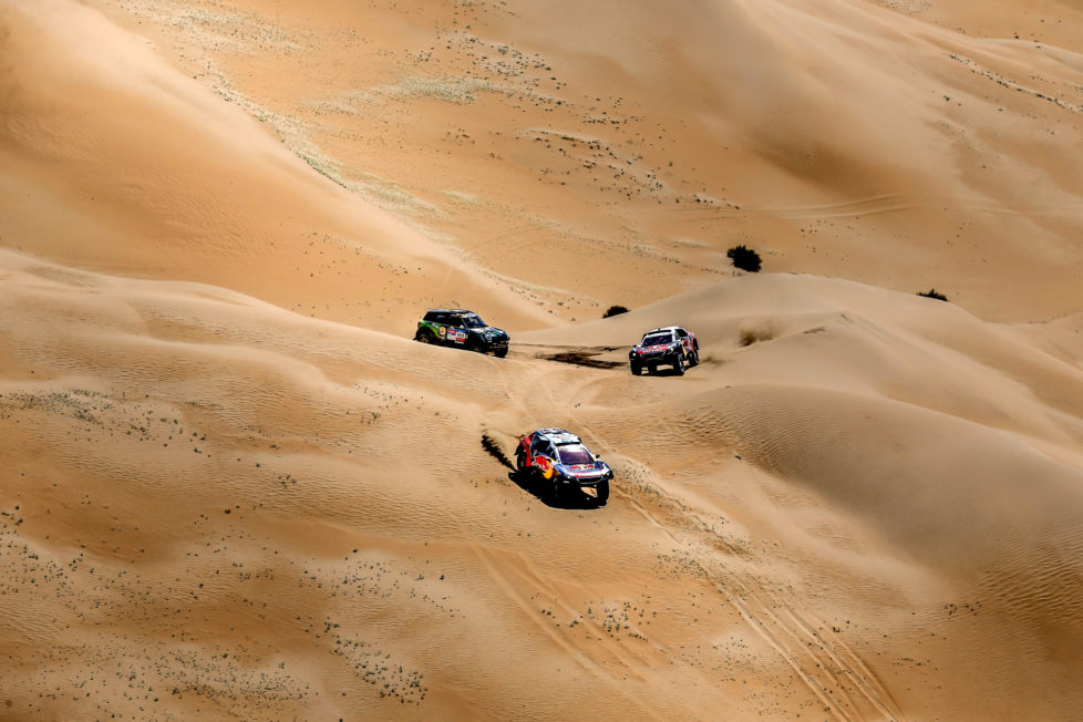 Mini team's Yazeed Mohamed al-Rhaji trails Peugeot team's Stephane Peterhansel and Cyril Despres during the 14th special stage of the Silkway rally in Inner Mongolia's Gobi desert near Wuhai. 130 competitors are racing over 10,734 kilometres crossing three countries and two continents from Moscow to Beijing. / AFP PHOTO / POOL / Bastien BAUDIN