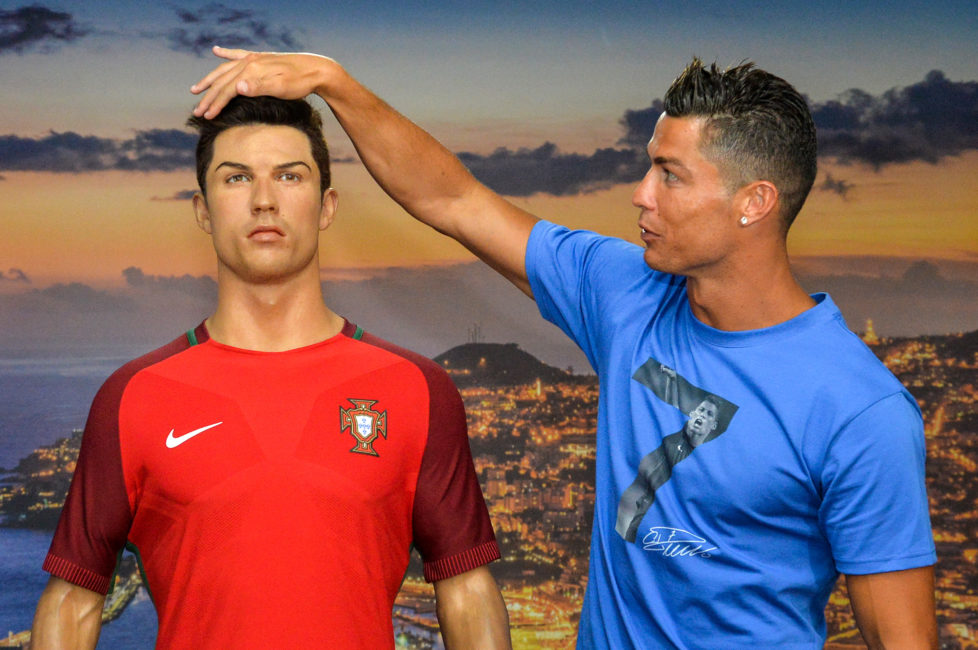 Portugese forward Cristiano Ronaldo poses next to a wax statue representing himself during a visit to the new location of the CR7 museum dedicated his professional career at Funchal, on the Portuguese island of Madeira on July 23, 2016. / AFP PHOTO / JOANA SOUSA