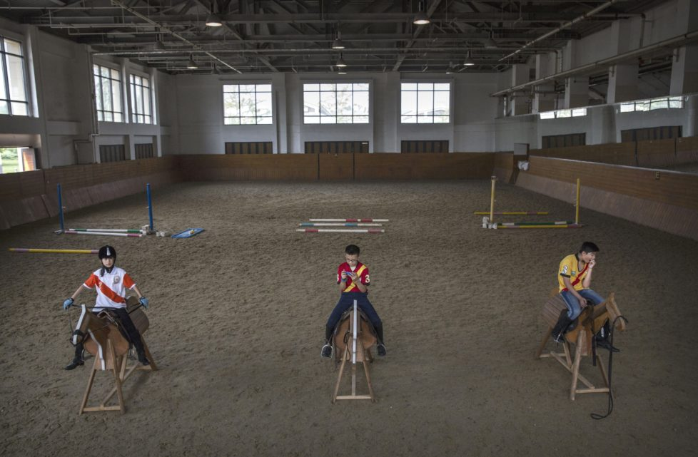 """TIANJIN, CHINA - JULY 16: Young Chinese players from the Junior Polo Programme sit on wooden horses during a summer training camp at the Tianjin Goldin Metropolitan Polo Club on July 16, 2016 in Tianjin, China. China's rising affluence has nurtured growing interest in polo and other past-times regarded as noble or prestigious by the country's elite. Clubs and international-size polo fields have been built in various cities including Beijing and Shanghai, and on the outskirts of Tianjin, where membership at the exclusive Goldin Metropolitan, China's largest polo club, is by invitation-only and fees can be significant for polo team owners. Increasingly, wealthy Chinese parents are choosing polo and other equestrian activities for their children as a way to bolster their credentials for admission to top-tier universities in the United States and the United Kingdom. While the so-called """"sport of kings"""" became a mainstay in Hong Kong during the era of British rule, polo is a relatively new sport to mainland China. Professional polo players are frequently flown in from countries such as New Zealand and Argentina in order to field competitive matches. Many of the polo clubs in China are tied to luxury real estate developments. (Photo by Kevin Frayer/Getty Images)"""