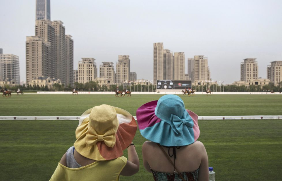 """TIANJIN, CHINA - JULY 17: Chinese spectators watch a match between Chinese players from the Metropolitan Polo Club team and visiting players from the United States and Britain during the intervarsity tounrament at the Tianjin Goldin Metropolitan Polo Club on July 17, 2016 in Tianjin, China. China's rising affluence has nurtured growing interest in polo and other past-times regarded as noble or prestigious by the country's elite. Clubs and international-size polo fields have been built in various cities including Beijing and Shanghai, and on the outskirts of Tianjin, where membership at the exclusive Goldin Metropolitan, China's largest polo club, is by invitation-only and fees can be significant for polo team owners. Increasingly, wealthy Chinese parents are choosing polo and other equestrian activities for their children as a way to bolster their credentials for admission to top-tier universities in the United States and the United Kingdom. While the so-called """"sport of kings"""" became a mainstay in Hong Kong during the era of British rule, polo is a relatively new sport to mainland China. Professional polo players are frequently flown in from countries such as New Zealand and Argentina in order to field competitive matches. Many of the polo clubs in China are tied to luxury real estate developments. (Photo by Kevin Frayer/Getty Images)"""