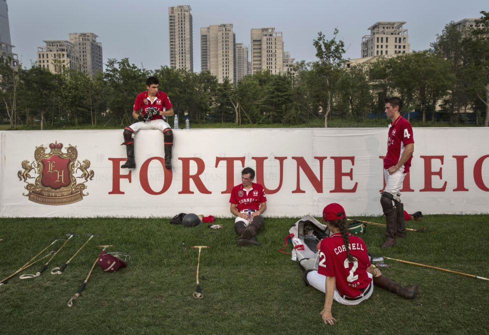 """TIANJIN, CHINA - JULY 17: Players from the Cornell University Polo team rest during a break in a match during the intervarsity tounrament at the Tianjin Goldin Metropolitan Polo Club on July 17, 2016 in Tianjin, China. China's rising affluence has nurtured growing interest in polo and other past-times regarded as noble or prestigious by the country's elite. Clubs and international-size polo fields have been built in various cities including Beijing and Shanghai, and on the outskirts of Tianjin, where membership at the exclusive Goldin Metropolitan, China's largest polo club, is by invitation-only and fees can be significant for polo team owners. Increasingly, wealthy Chinese parents are choosing polo and other equestrian activities for their children as a way to bolster their credentials for admission to top-tier universities in the United States and the United Kingdom. While the so-called """"sport of kings"""" became a mainstay in Hong Kong during the era of British rule, polo is a relatively new sport to mainland China. Professional polo players are frequently flown in from countries such as New Zealand and Argentina in order to field competitive matches. Many of the polo clubs in China are tied to luxury real estate developments. (Photo by Kevin Frayer/Getty Images)"""