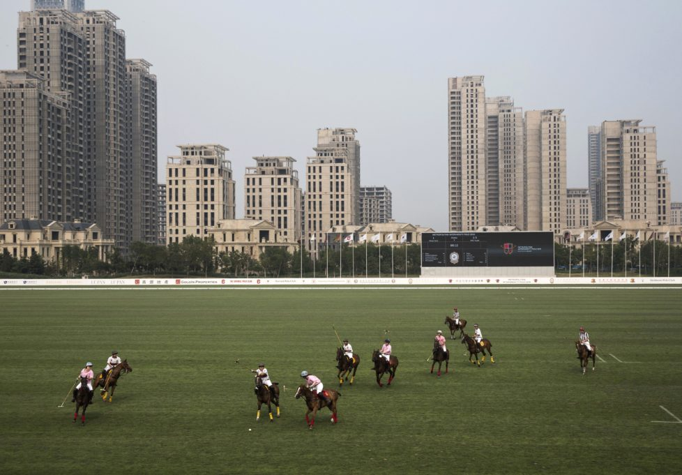 "TIANJIN, CHINA - JULY 17: Chinese players from the Metropolitan Polo Club team, in white, and players from the United States and Great Britain play an exhibiton match at the Tianjin Goldin Metropolitan Polo Club on July 17, 2016 in Tianjin, China. China's rising affluence has nurtured growing interest in polo and other past-times regarded as noble or prestigious by the country's elite. Clubs and international-size polo fields have been built in various cities including Beijing and Shanghai, and on the outskirts of Tianjin, where membership at the exclusive Goldin Metropolitan, China's largest polo club, is by invitation-only and fees can be significant for polo team owners. Increasingly, wealthy Chinese parents are choosing polo and other equestrian activities for their children as a way to bolster their credentials for admission to top-tier universities in the United States and the United Kingdom. While the so-called ""sport of kings"" became a mainstay in Hong Kong during the era of British rule, polo is a relatively new sport to mainland China. Professional polo players are frequently flown in from countries such as New Zealand and Argentina in order to field competitive matches. Many of the polo clubs in China are tied to luxury real estate developments. (Photo by Kevin Frayer/Getty Images)"