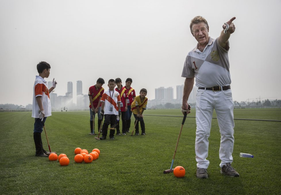 TIANJIN, CHINA - JULY 17: Derek Reid, Director of Polo Operations, right, gestures as he instructs young Chinese players from the Junior Polo Programme during stick and ball training during summer camp at the Tianjin Goldin Metropolitan Polo Club on July 17, 2016 in Tianjin, China. ChinaÍs rising affluence has nurtured growing interest in polo and other past-times regarded as noble or prestigious by the countryÍs elite.æ Clubs and international-size polo fields have been built in various cities including Beijing and Shanghai, and on the outskirts of Tianjin, where membership at the exclusive Goldin Metropolitan, ChinaÍs largest polo club, is by invitation-only and fees can be significant for polo team owners.æIncreasingly, wealthy Chinese parents are choosing polo and other equestrian activities for their children as a way to bolster their credentials for admission to top-tier universities in the United States and the United Kingdom.æ While the so-called ïsport of kingsÍ became a mainstay in Hong Kong during the era of British rule, polo is a relatively new sport to mainland China. æProfessional polo players are frequently flown in from countries such as New Zealand and Argentina in order to field competitive matches.æMany of the polo clubs in China are tied to luxury real estate developments. (Photo by Kevin Frayer/Getty Images)