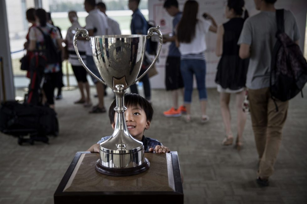 """TIANJIN, CHINA - JULY 17: A Chinese boy looks at the cup before tournament play at the Tianjin Goldin Metropolitan Polo Club on July 17, 2016 in Tianjin, China. China's rising affluence has nurtured growing interest in polo and other past-times regarded as noble or prestigious by the country's elite. Clubs and international-size polo fields have been built in various cities including Beijing and Shanghai, and on the outskirts of Tianjin, where membership at the exclusive Goldin Metropolitan, China's largest polo club, is by invitation-only and fees can be significant for polo team owners. Increasingly, wealthy Chinese parents are choosing polo and other equestrian activities for their children as a way to bolster their credentials for admission to top-tier universities in the United States and the United Kingdom. While the so-called """"sport of kings"""" became a mainstay in Hong Kong during the era of British rule, polo is a relatively new sport to mainland China. Professional polo players are frequently flown in from countries such as New Zealand and Argentina in order to field competitive matches. Many of the polo clubs in China are tied to luxury real estate developments. (Photo by Kevin Frayer/Getty Images)"""