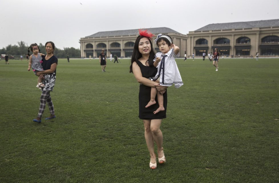 """TIANJIN, CHINA - JULY 16: A Chinese woman walks across the field with their children during a break in an intervarsity tournament match at the Tianjin Goldin Metropolitan Polo Club on July 16, 2016 in Tianjin, China. China's rising affluence has nurtured growing interest in polo and other past-times regarded as noble or prestigious by the country's elite. Clubs and international-size polo fields have been built in various cities including Beijing and Shanghai, and on the outskirts of Tianjin, where membership at the exclusive Goldin Metropolitan, China's largest polo club, is by invitation-only and fees can be significant for polo team owners. Increasingly, wealthy Chinese parents are choosing polo and other equestrian activities for their children as a way to bolster their credentials for admission to top-tier universities in the United States and the United Kingdom. While the so-called """"sport of kings"""" became a mainstay in Hong Kong during the era of British rule, polo is a relatively new sport to mainland China. Professional polo players are frequently flown in from countries such as New Zealand and Argentina in order to field competitive matches. Many of the polo clubs in China are tied to luxury real estate developments. (Photo by Kevin Frayer/Getty Images)"""