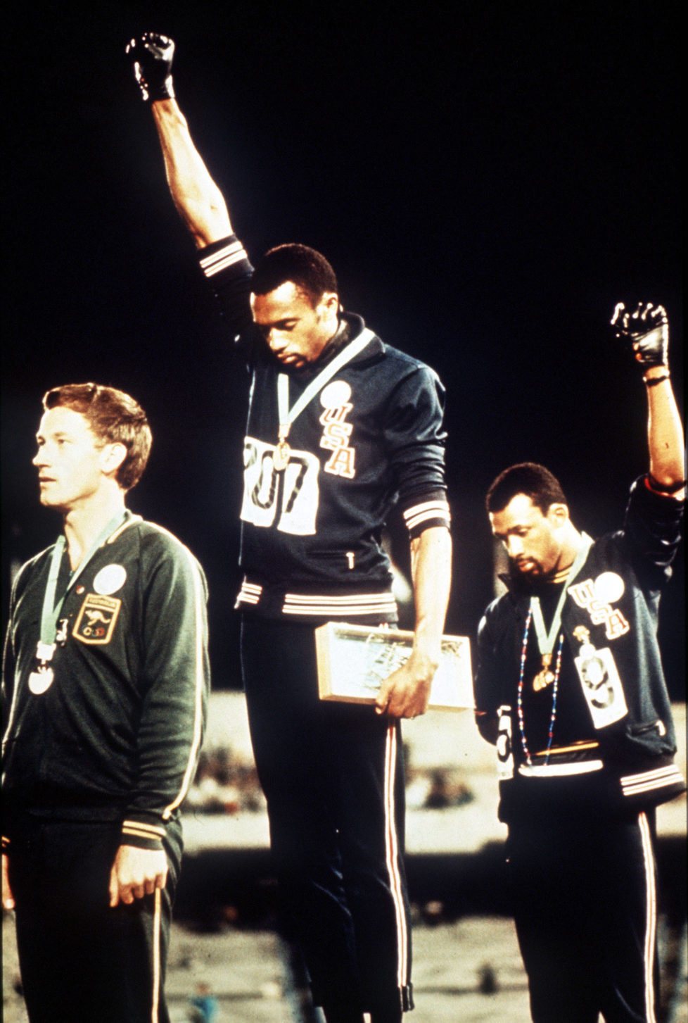 1968 Olympic Games, Mexico City, Mexico, Men's 200 Metres Final, USA gold medallist Tommie Smith (C) and bronze medallist John Carlos give the black power salutes as an anti-racial protest as they stand on the podium with Australian silver medallist Peter Norman (Photo by Rolls Press/Popperfoto/Getty Images)
