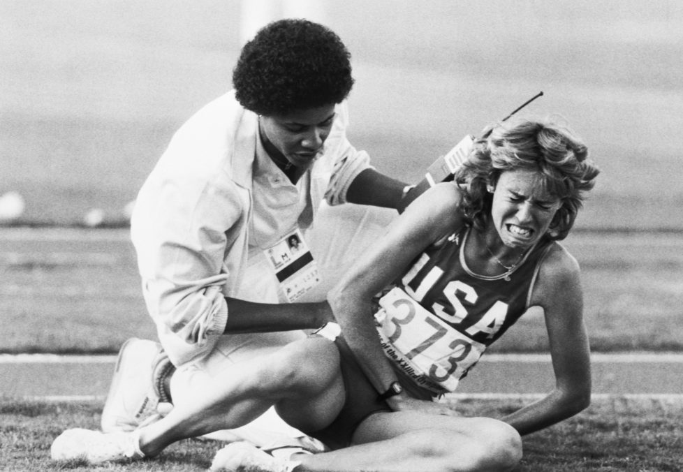 A track official attempts to comfort a crying Mary Decker after Decker's fall in the women's 3000-meter run at the 1984 Summer Olympics. Decker fell after becoming entangled with South African Zola Budd during the course of the race. Los Angeles, California, August 10, 1984.