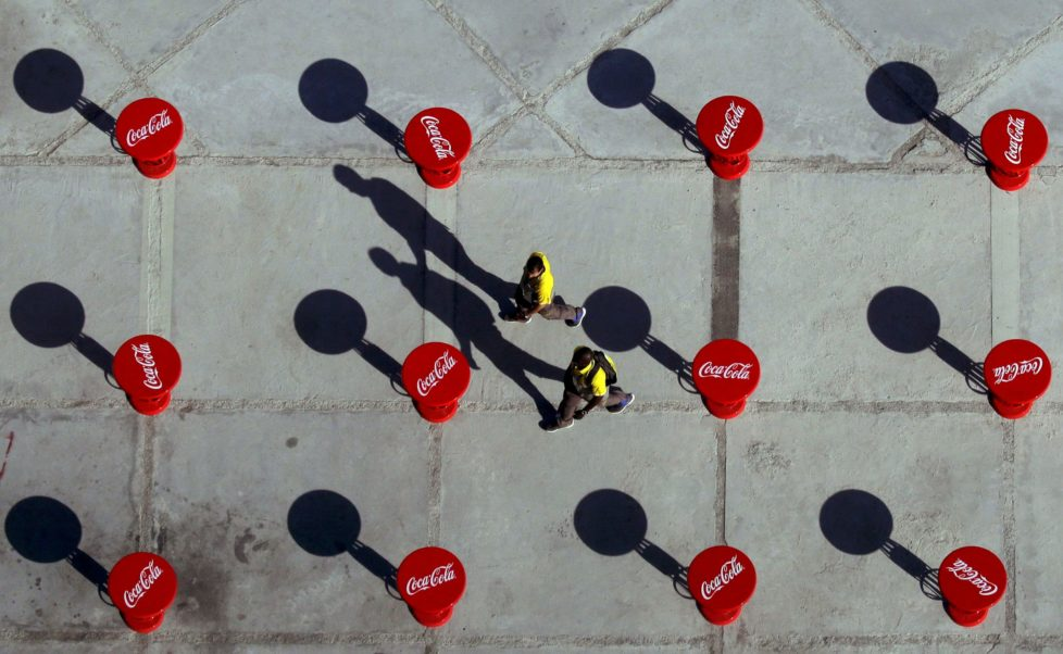2016 Rio Olympics - Olympic Park - Rio de Janeiro, Brazil - 31/07/2016. Volunteers walk between Coca Cola branded tables near the main press centre and broadcast centre. REUTERS/Kevin Coombs TPX IMAGES OF THE DAY