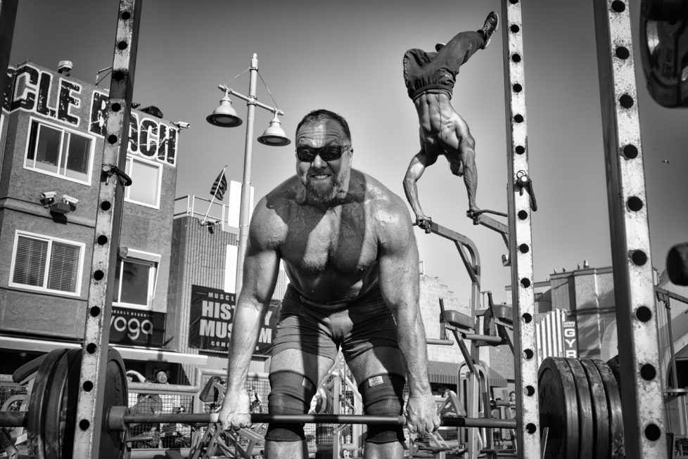 A weightlifter lifts a barbell loaded with heavy plates while a bodybuilder performs an aerial handstand at the Muscle Beach Gym in Venice Beach, CA.
