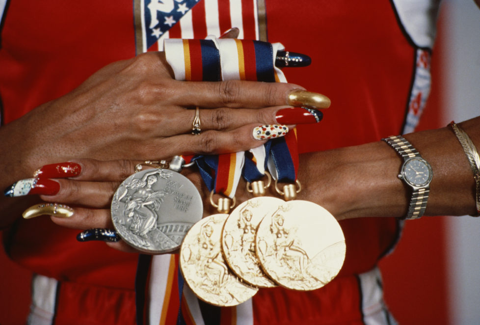 Oct 1988: Florence Griffith-Joyner of the USA displays her three gold medals and a silver medal that she won at the 1988 Summer Olympics in Seoul, Korea. Griffith-Joyner won gold medals in the 100m, 200m and the 4x100m relay. Mandatory Credit: Tony Du