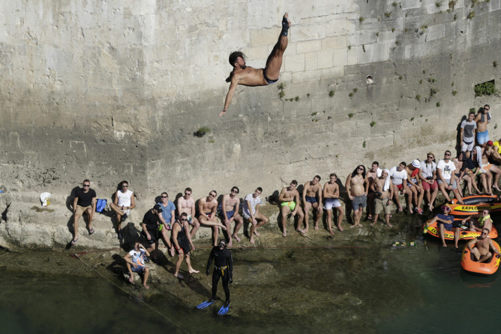 Spectators watch as a diver jumps from the Old Mostar Bridge during the Red Bull Cliff Diving World Series 2016, in Mostar, 140 kms south of Bosnian capital of Sarajevo, Saturday, Sept. 24, 2016. Twenty one of the world's best competitors took part in the competition diving from a 28 meter high bridge over the river of Neretva. Michal Navrtil from Czech republic took first place in this competition.(AP Photo/Amel Emric)