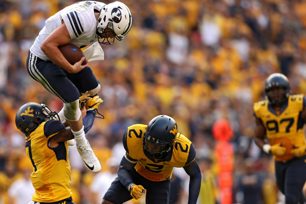 LANDOVER, MD - SEPTEMBER 24: Quarterback Taysom Hill #7 of the Brigham Young Cougars jumps between Khairi Sharif #7 (L) and Jeremy Tyler #2 (R) of the West Virginia Mountaineers during the second half at FedExField on September 24, 2016 in Landover, Maryland. (Photo by Patrick Smith/Getty Images)