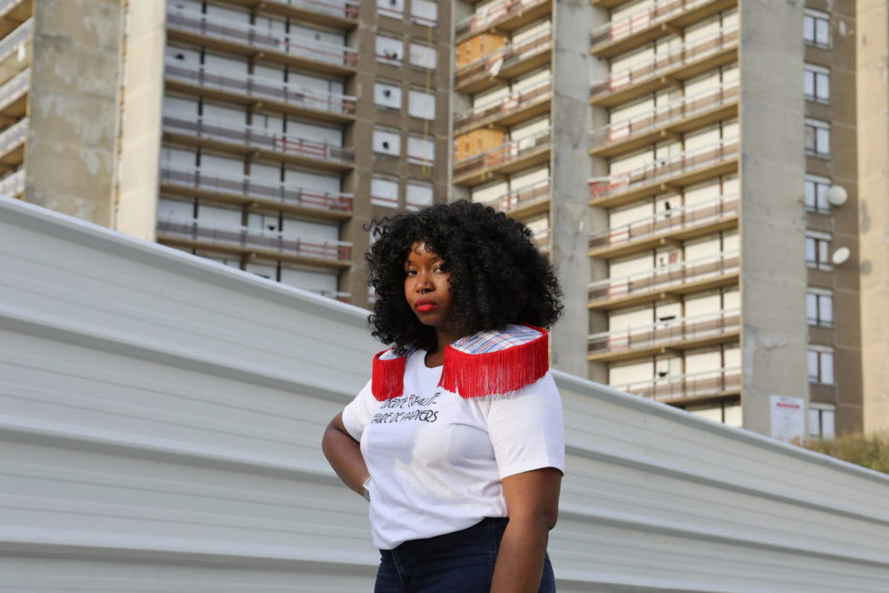 """Designer Aisse N'diaye poses for a picture wearing a shirt from her brand Afrikanista in Clichy-sous-Bois, France, August 26, 2016. N'diaye grew up in Clichy-sous-bois, where her parents currently reside. Behind her is the La Forestiere housing where she grew up, and which is now slated for demolition. REUTERS/Joe Penney SEARCH """"CREATIVE BANLIEUE"""" FOR THIS STORY. SEARCH """"WIDER IMAGE"""" FOR ALL STORIES. THE IMAGES SHOULD ONLY BE USED TOGETHER WITH THE STORY - NO STAND-ALONE USES."""