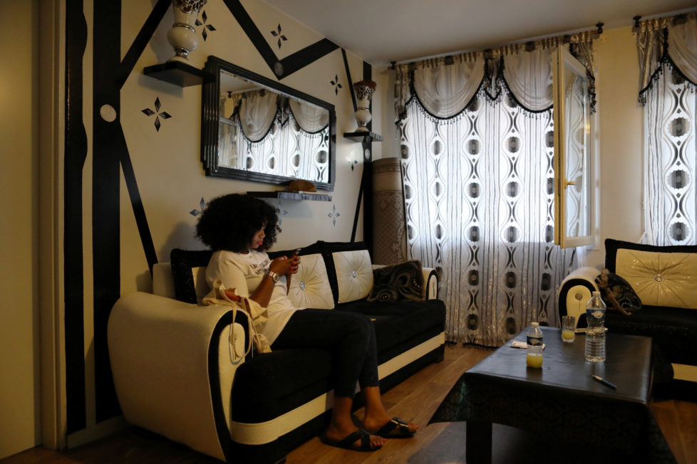"""Designer Aisse Ndiaye, owner of the clothing brand Afrikanista, sits on the couch at her parents' house in Clichy-sous-Bois, France, August 26, 2016. REUTERS/Joe Penney SEARCH """"CREATIVE BANLIEUE"""" FOR THIS STORY. SEARCH """"WIDER IMAGE"""" FOR ALL STORIES. THE IMAGES SHOULD ONLY BE USED TOGETHER WITH THE STORY - NO STAND-ALONE USES."""