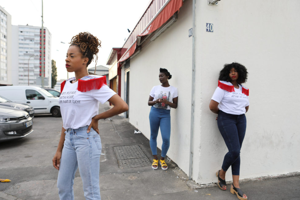 """Designer Aisse N'diaye (R) and friends Sandrine Alcan (L) and Virginie Ehonian (C) wear T-shirts from N'diaye's brand Afrikanista in Clichy-sous-bois, France, August 26, 2016. N'diaye grew up in Clichy-sous-bois, where her parents currently live. REUTERS/Joe Penney SEARCH """"CREATIVE BANLIEUE"""" FOR THIS STORY. SEARCH """"WIDER IMAGE"""" FOR ALL STORIES. THE IMAGES SHOULD ONLY BE USED TOGETHER WITH THE STORY - NO STAND-ALONE USES."""