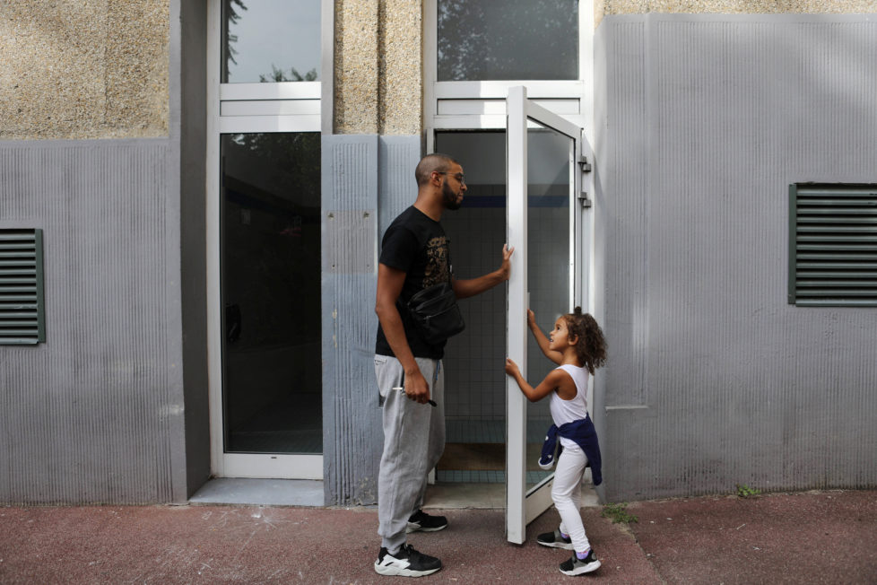 """Rapper Worms-T walks with his daughter to his apartment building in Pantin, France, September 2, 2016. REUTERS/Joe Penney SEARCH """"CREATIVE BANLIEUE"""" FOR THIS STORY. SEARCH """"WIDER IMAGE"""" FOR ALL STORIES. THE IMAGES SHOULD ONLY BE USED TOGETHER WITH THE STORY - NO STAND-ALONE USES."""