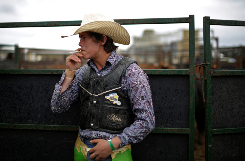 """Bull rider Tom Phibbs, 21, from Chiltern, smokes a cigarette before competing at the Deni Ute Muster in Deniliquin, New South Wales, September 30, 2016. REUTERS/Jason Reed SEARCH """"UTE CULTURE"""" FOR THIS STORY. SEARCH """"THE WIDER IMAGE"""" FOR ALL STORIES."""