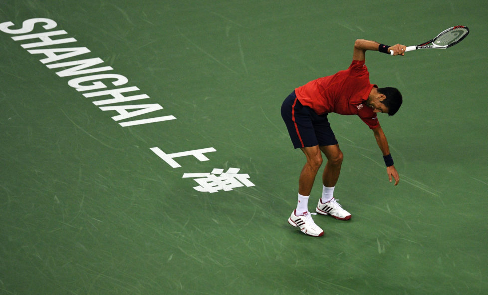 Novak Djokovic of Serbia smashes his racket after losing a point against Roberto Bautista Agut of Spain in their men's singles semi-finals match at the Shanghai Masters tennis tournament in Shanghai on October 15, 2016. / AFP PHOTO / JOHANNES EISELE