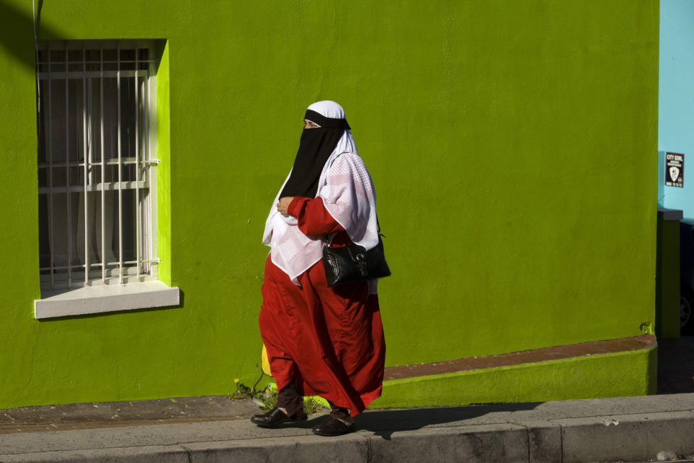 CAPE TOWN, SOUTH AFRICA - SEPTEMBER 30 - A Muslim woman walks past a brightly-painted building in this Cape Malay neighborhood called Bo Kaap. (Photo by Melanie Stetson Freeman/The Christian Science Monitor/Getty Images)